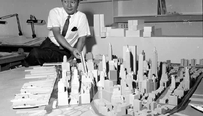 Architect Minoru Yamasaki stands behind an architectural model of New York City, 1958.